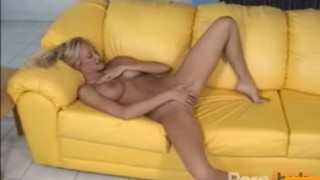 Busty mature masturbates on the couch