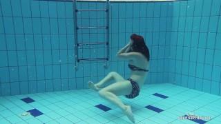 Redheaded Katrin stripping underwater